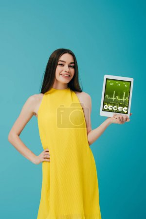 Photo for Smiling brunette girl in yellow dress showing digital tablet with healthcare app isolated on turquoise - Royalty Free Image