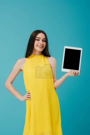 beautiful brunette girl in yellow dress with hand on hip showing digital tablet with blank screen isolated on turquoise