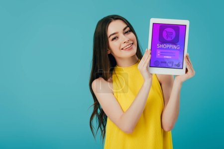 beautiful happy girl in yellow dress showing digital tablet with shopping app isolated on turquoise