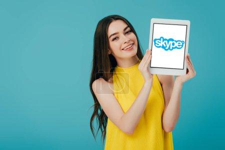 Photo pour KYIV, UKRAINE - 6 JUIN 2019 : heureuse belle fille en robe jaune montrant tablette numérique avec application skype isolée sur turquoise - image libre de droit