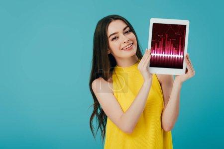 Foto de Hermosa chica feliz en vestido amarillo mostrando tableta digital con aplicación de comercio aislado en turquesa - Imagen libre de derechos