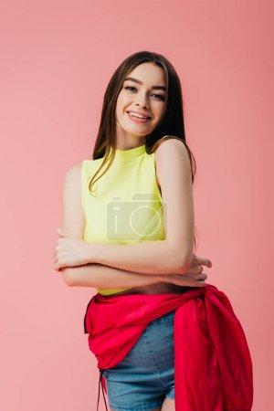 Photo pour Belle fille de sourire dans des vêtements lumineux avec les bras croisés d'isolement sur le rose - image libre de droit