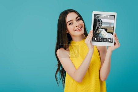 schönes Mädchen in gelbem Kleid zeigt digitales Tablet mit Ticket-App isoliert auf Türkis