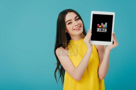 Photo pour KYIV, UKRAINE - 6 JUIN 2019 : heureuse belle fille en robe jaune montrant tablette numérique avec application Deezer isolé sur turquoise - image libre de droit