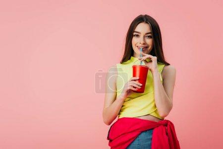 Photo pour Belle fille souriante en vêtements lumineux boire soda de paille isolé sur rose - image libre de droit