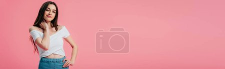 Photo pour Belle fille souriante posant avec la main sur la hanche isolé sur rose, panoramique - image libre de droit