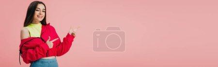 Photo pour Belle fille souriante en vêtements lumineux pointant avec les doigts à l'espace de copie isolé sur rose, plan panoramique - image libre de droit