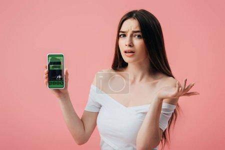 Foto de Hermosa chica confundida sosteniendo teléfono inteligente con la aplicación de reserva en línea del hotel y mostrando gesto de encogimiento de hombros aislado en rosa - Imagen libre de derechos