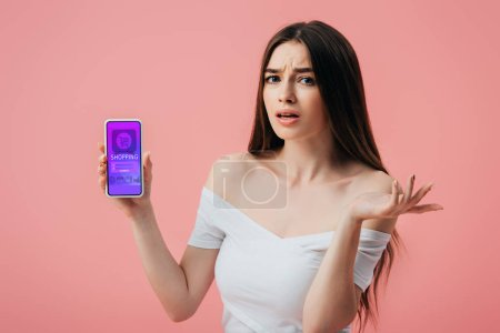Foto de Hermosa chica confundida sosteniendo el teléfono inteligente con la aplicación de compras en línea y mostrando el gesto de encogimiento de hombros aislado en rosa - Imagen libre de derechos