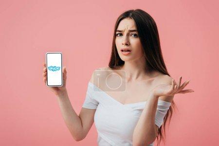 Foto de Kiev, Ucrania - 6 de junio de 2019: hermosa chica confundida sosteniendo teléfono inteligente con la aplicación de Skype y mostrando gesto de encogimiento de hombros aislado en rosa - Imagen libre de derechos