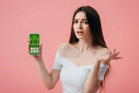 Foto de Hermosa chica confundida sosteniendo teléfono inteligente con aplicación de estilo de vida saludable y mostrando gesto de encogimiento de hombros aislado en rosa - Imagen libre de derechos