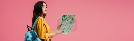 Photo pour Tir panoramique de fille rêveuse avec la carte de fixation de sac à dos et regardant loin isolé sur le rose - image libre de droit
