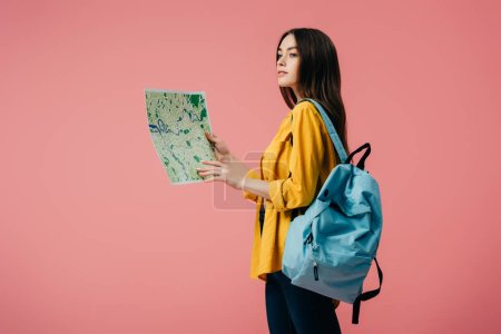 Photo pour Fille rêveuse avec la carte de fixation de sac à dos et regardant loin d'isolement sur le rose - image libre de droit