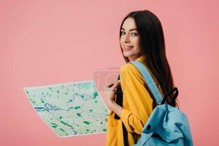 Photo pour Belle fille de sourire avec la carte d'impression de fixation de sac à dos d'isolement sur le rose - image libre de droit