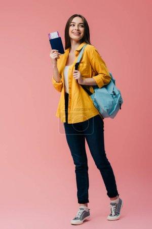 Photo pour Vue pleine longueur de belle fille de sourire avec le passeport de fixation de sac à dos avec le billet d'avion d'isolement sur le rose - image libre de droit