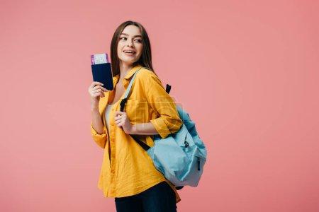 Photo pour Belle fille de sourire avec le passeport de fixation de sac à dos avec le billet d'avion d'isolement sur le rose - image libre de droit