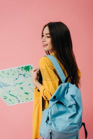 Photo pour Belle fille souriante avec sac à dos tenant carte isolé sur rose - image libre de droit