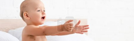 Photo for Panoramic shot of adorable little child opening mouth and raising hands forward in white room - Royalty Free Image