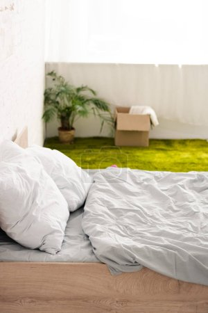 Photo for Bed with white bedclothes near green carpet with cardboard box - Royalty Free Image