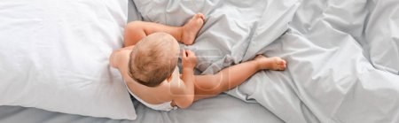 Photo for Panoramic shot of little barefoot child sitting on bed with white bedding - Royalty Free Image