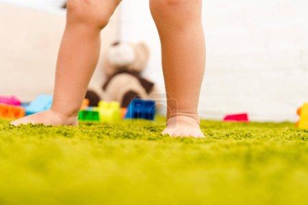 Foto de Vista recortada del niño descalzo de pie en el suelo verde entre juguetes coloridos - Imagen libre de derechos