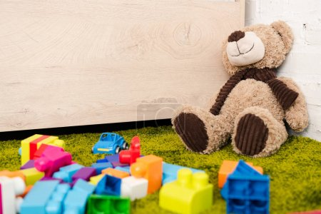 Plush bear and scattered pieces of construction on green carpet