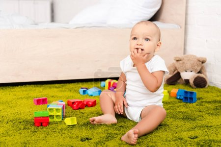 Cute little kid sitting surrounded wuth toys on green floor
