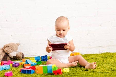 Photo pour Enfant d'adorbale s'asseyant parmi des jouets sur le plancher vert et retenant l'appareil numérique - image libre de droit
