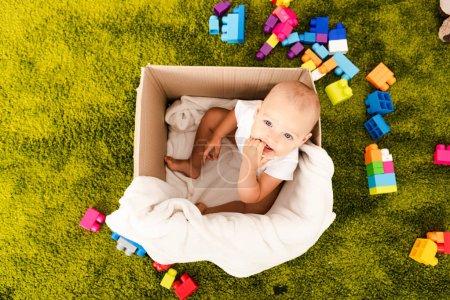 Photo pour Vue du dessus du mignon petit enfant assis dans une boîte en carton avec couverture blanche sur le sol vert - image libre de droit