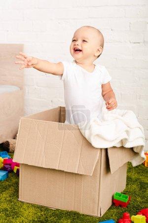 Photo pour Petit enfant heureux restant dans la boîte en carton et soulevant la main - image libre de droit