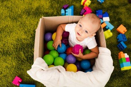 Foto de Vista superior del niño lindo en la caja de cartón jugando con bolas de colores - Imagen libre de derechos