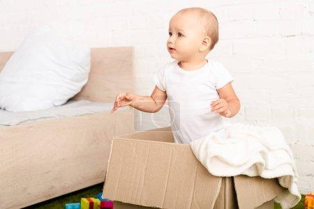Photo pour Petit enfant restant dans la boîte en carton avec la couverture blanche et regardant loin - image libre de droit