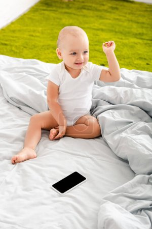Adorable little child sitting on bed near digital device and raising hand up