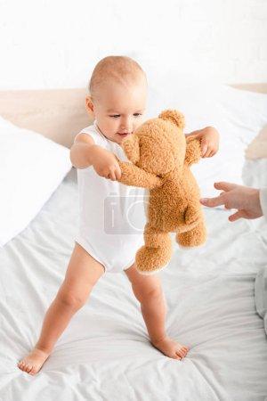 Photo pour Enfant nu-pieds mignon dans des vêtements blancs jouant avec son ours de nounours sur le lit - image libre de droit