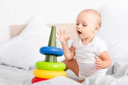 Foto de Lindo niño pequeño con ropa blanca sentado en la cama y jugando con pirámide de juguete - Imagen libre de derechos