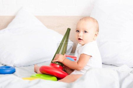 Foto de Adorable niño pequeño con ropa blanca sentado en la cama y sosteniendo pirámide de juguete de colores - Imagen libre de derechos