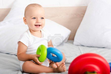 Photo for Cute little child with smile sitting on bed and holding colorful toy rings - Royalty Free Image