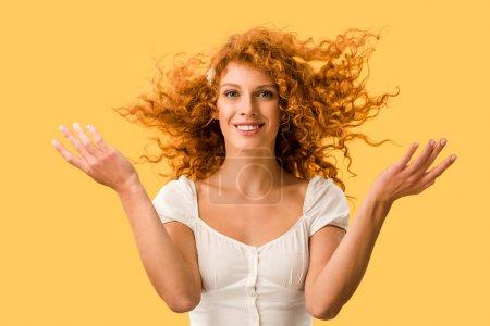 Photo pour Femme heureuse avec le cheveu rouge bouclé, d'isolement sur le jaune - image libre de droit
