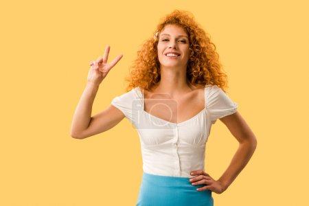 Photo pour Femme souriante aux cheveux roux montrant le symbole de victoire isolé sur jaune - image libre de droit