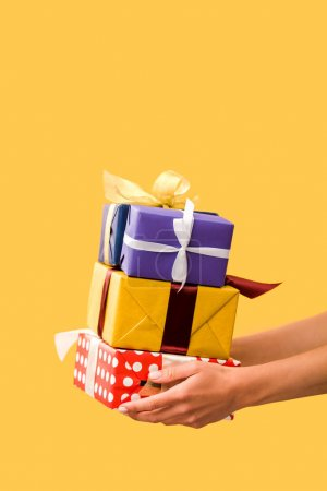 cropped view of girl holding presents in hands isolated on yellow