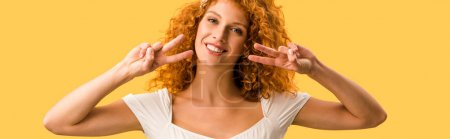 Photo pour Femme de sourire avec le cheveu rouge affichant des symboles de paix d'isolement sur le jaune - image libre de droit