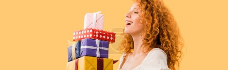 laughing redhead girl holding presents isolated on yellow