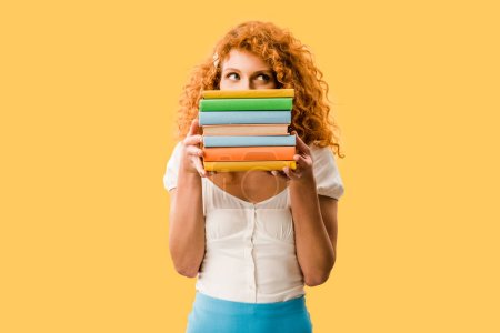 Photo for Attractive female student holding books isolated on yellow - Royalty Free Image
