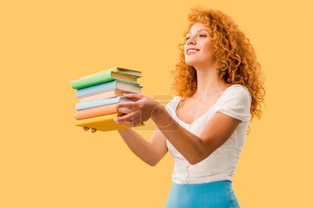 Photo pour Étudiant de sourire attrayant retenant des livres d'isolement sur le jaune - image libre de droit
