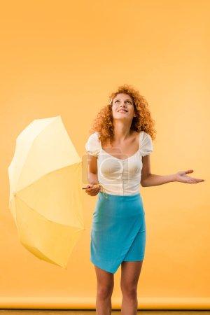 Photo pour Femme attirante de rousse posant avec le parapluie d'isolement sur le jaune - image libre de droit