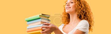 Photo pour Étudiant heureux de fixation de rousse retenant des livres d'isolement sur le jaune - image libre de droit