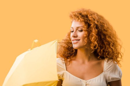 Photo for Smiling redhead woman posing with umbrella isolated on yellow - Royalty Free Image
