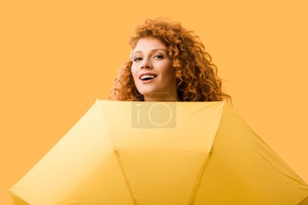 smiling redhead girl posing with umbrella isolated on yellow