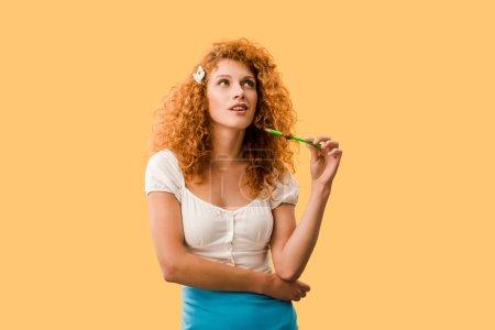 Photo pour Femme rousse réfléchie avec crayon isolé sur jaune - image libre de droit