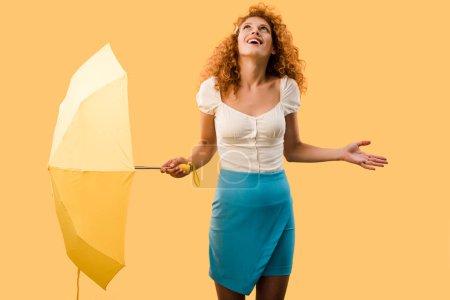 Photo pour Heureuse femme bouclée posant avec parapluie isolé sur jaune - image libre de droit